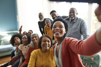 Young woman takes a selfie with family and friends during a holiday celebration.