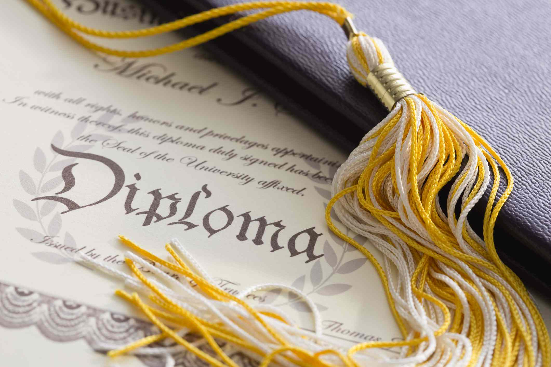 Close-up view of graduation tassel and diploma for sales and marketing