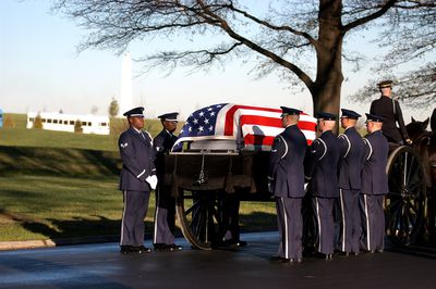 Soldiers carrying a coffin covered with a flag.