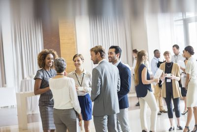 People in business casual dress mingling at a college networking event.