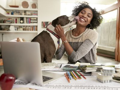 dog licking woman's face sitting in front of a computer