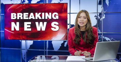 News anchor in television studio reading the news
