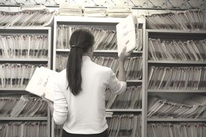 Health Services manager pulling medical records from a file in a doctor's office.