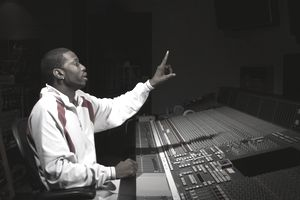 Man seated at mixing board gesturing