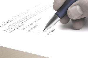 Close up of a hand signing a business letter