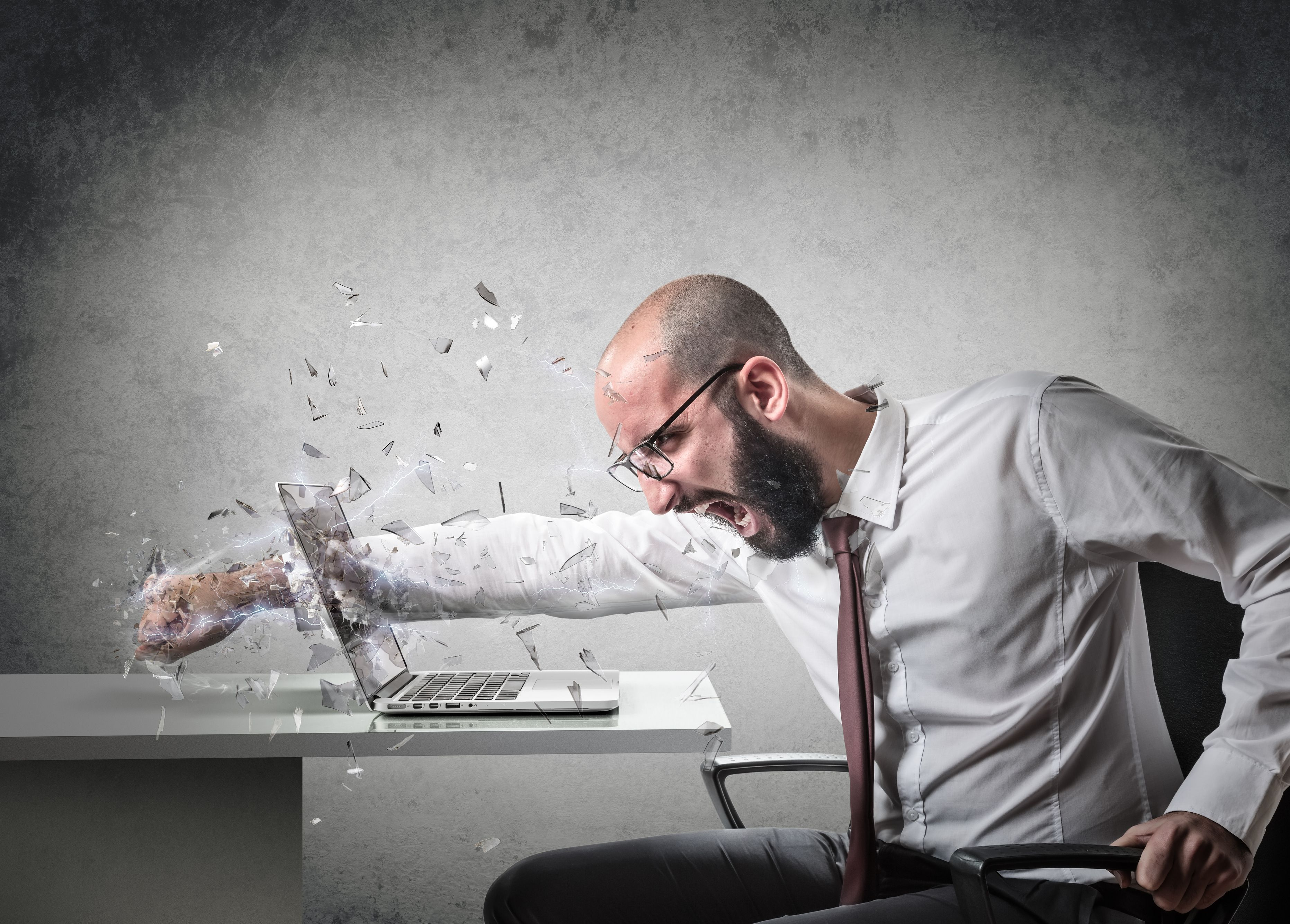 Person putting fist through computer screen in explosion of anger