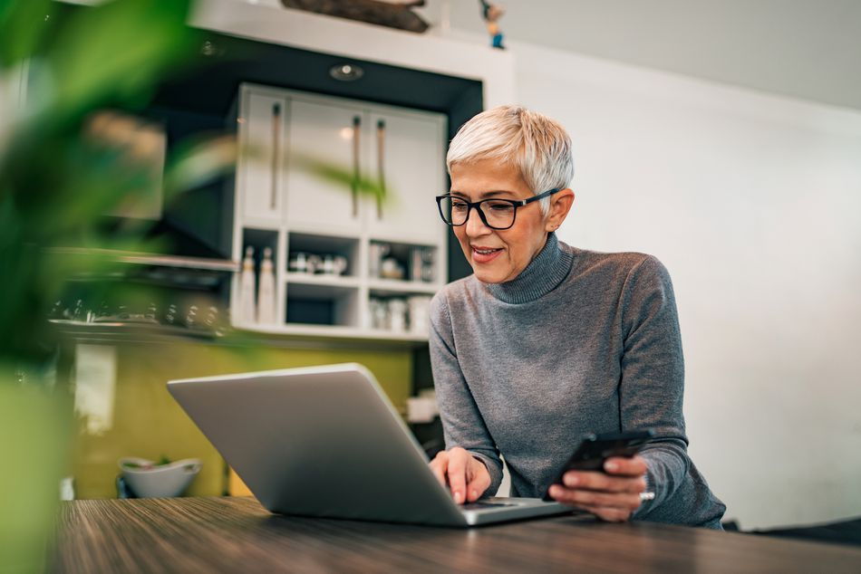 Modern mature woman using laptop and smart phone at home, portrait.
