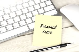 Personal leave on sticky note on work desk