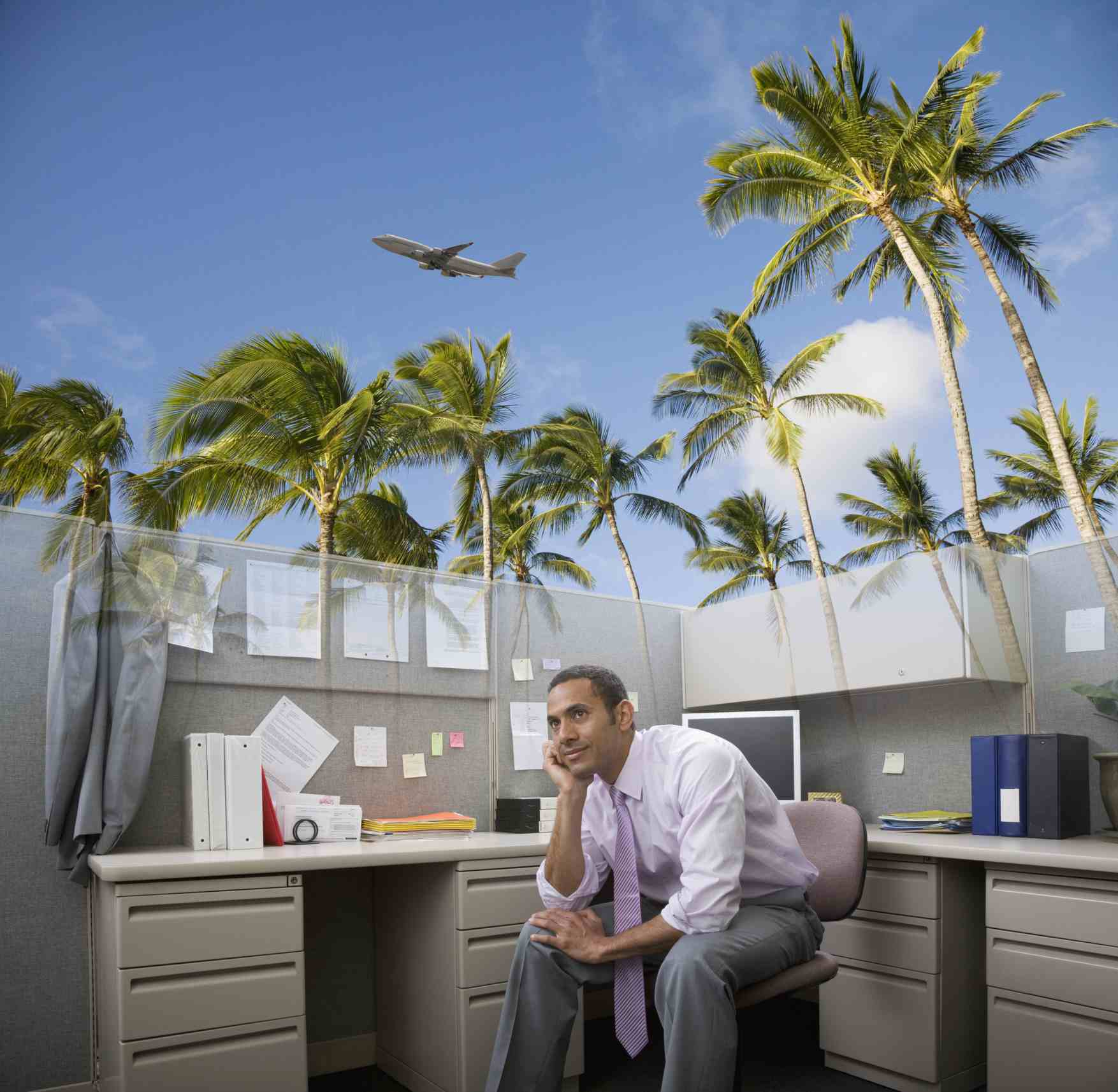 Man in cubicle dreaming of paradise
