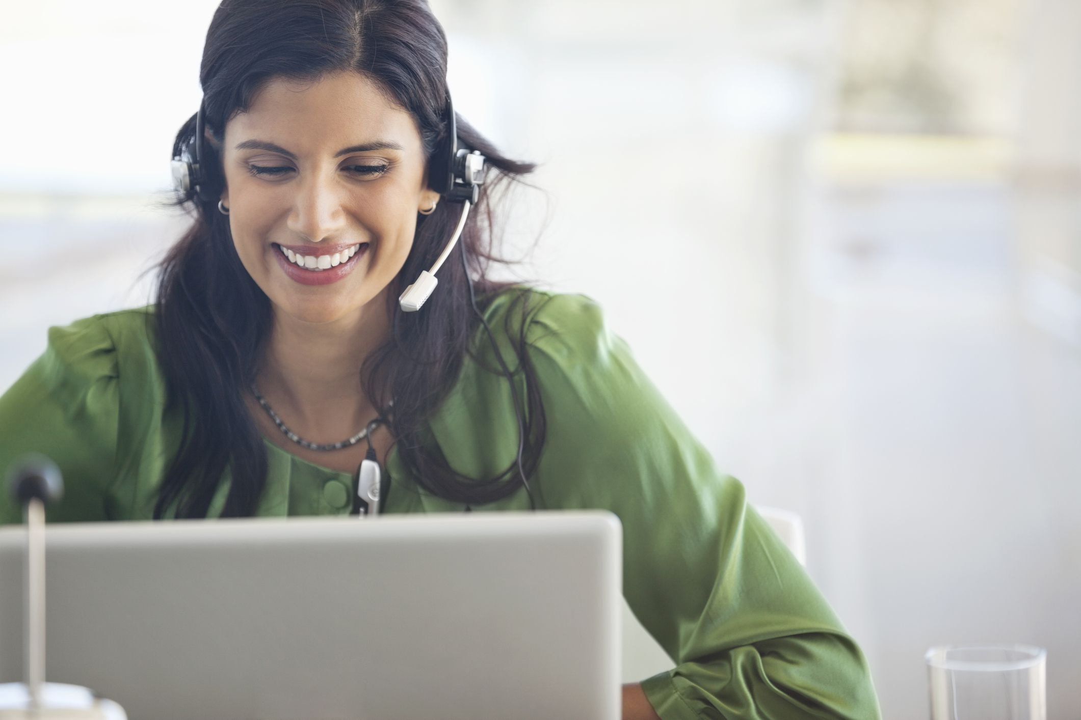 Close up of a part-time call center representative on laptop with headset
