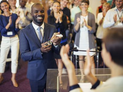 Black male employee is formally recognized for his contribution with a recognition trophy.