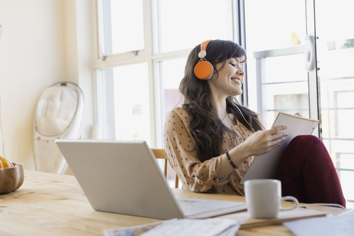 Woman with headphones and notebook at laptop