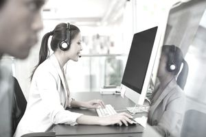 businesswoman with headset at computer in office