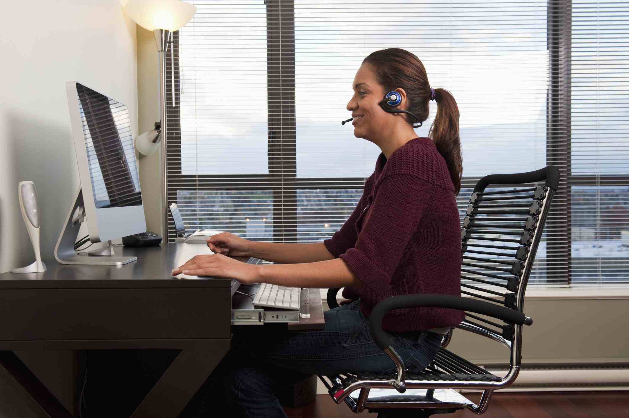 Call center employee working from their apartment sitting at a desk by a window.