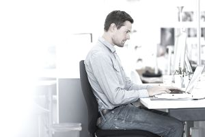 A man in business casual clothing on a laptop