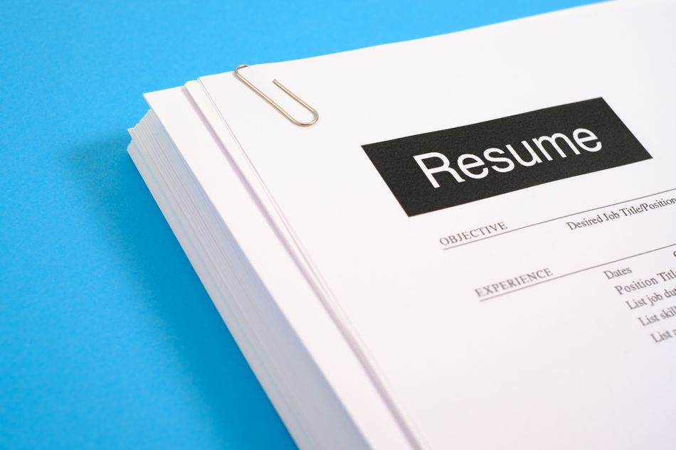A stack of resumes on a blue desk.