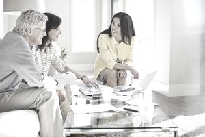 Female financial adviser working with couple in home