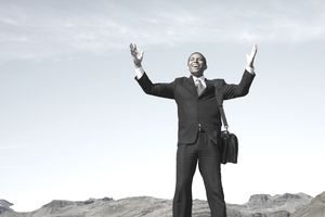 Businessman smiling with hands raised as he celebrates his persistence and determination in reaching the top of the hill.