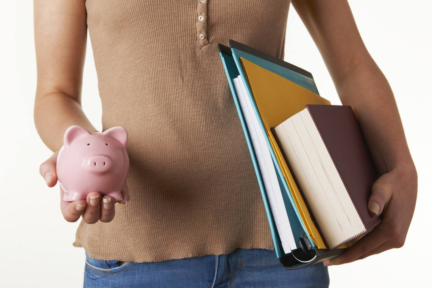 person holding a piggy bank in one hand and school books in the other