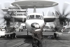 Aviation Electronics Technician directs an E-2C Hawkeye to start its engines