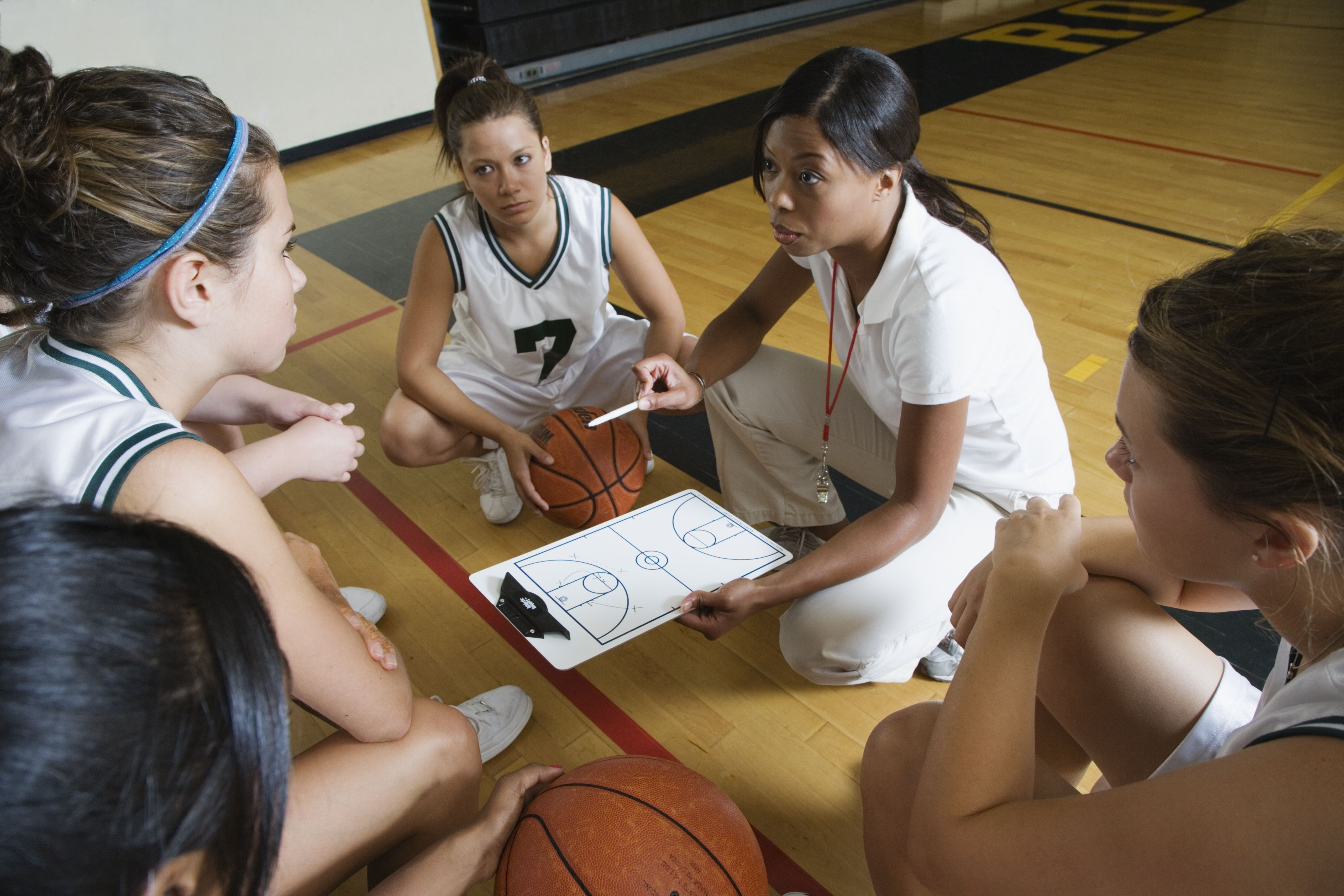 Basketball coach talking with students in a gym