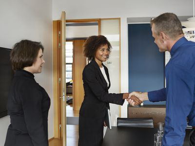 Hiring manager shaking hands with a prospective salesperson in an interview.