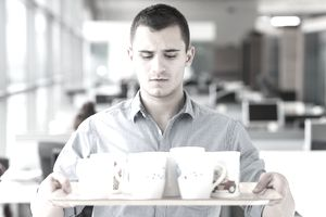young man holding tray of coffee mugs