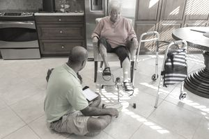 Physical therapist assistant treating a senior patient
