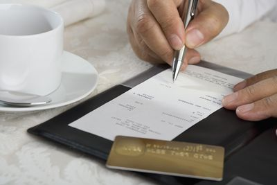 Business etiquette when to introduce someone as miss mrs or ms close up of man signing credit card receipt at restaurant reheart Image collections
