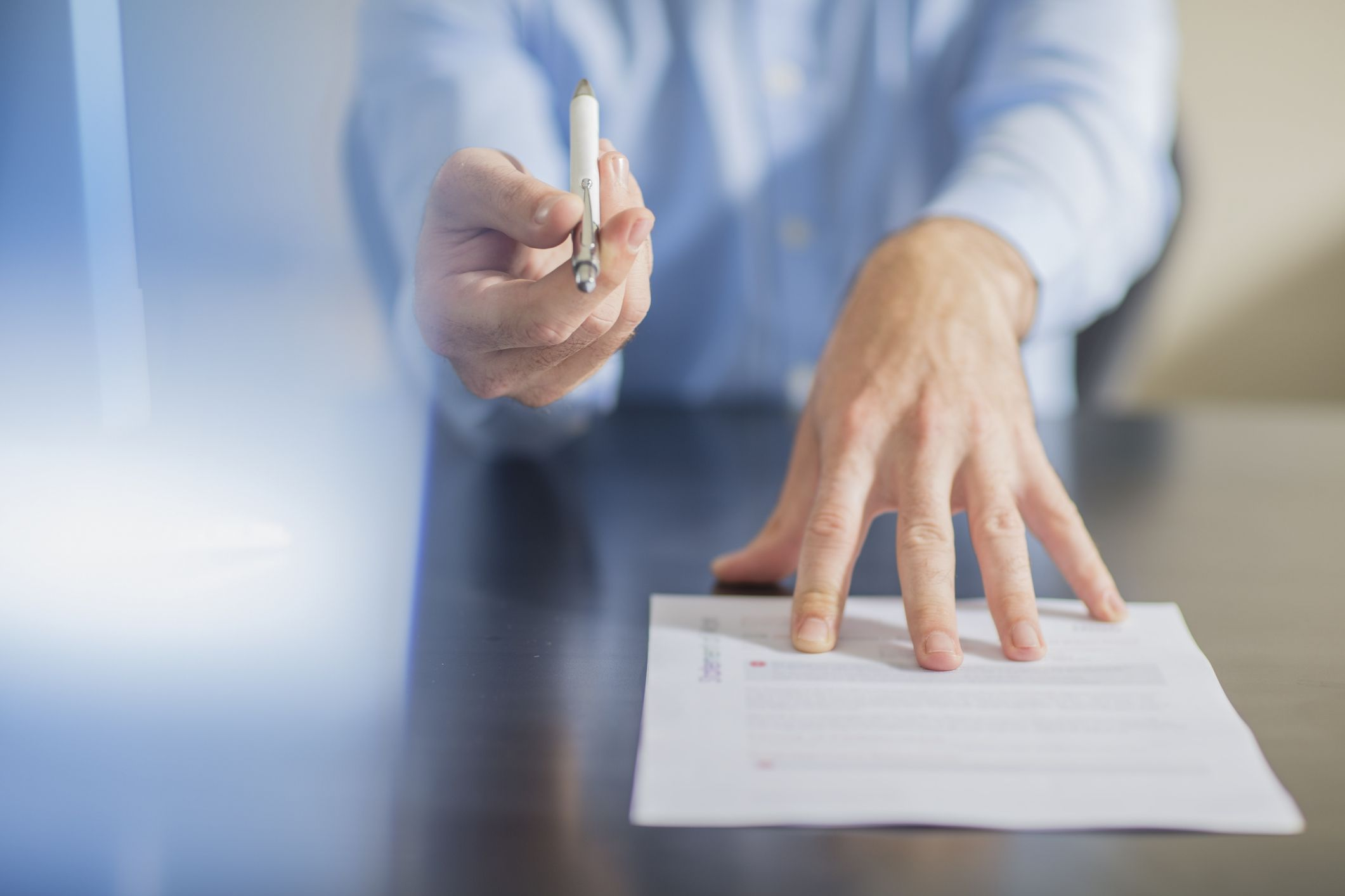 Person sitting at office desk presenting ballpen and contract