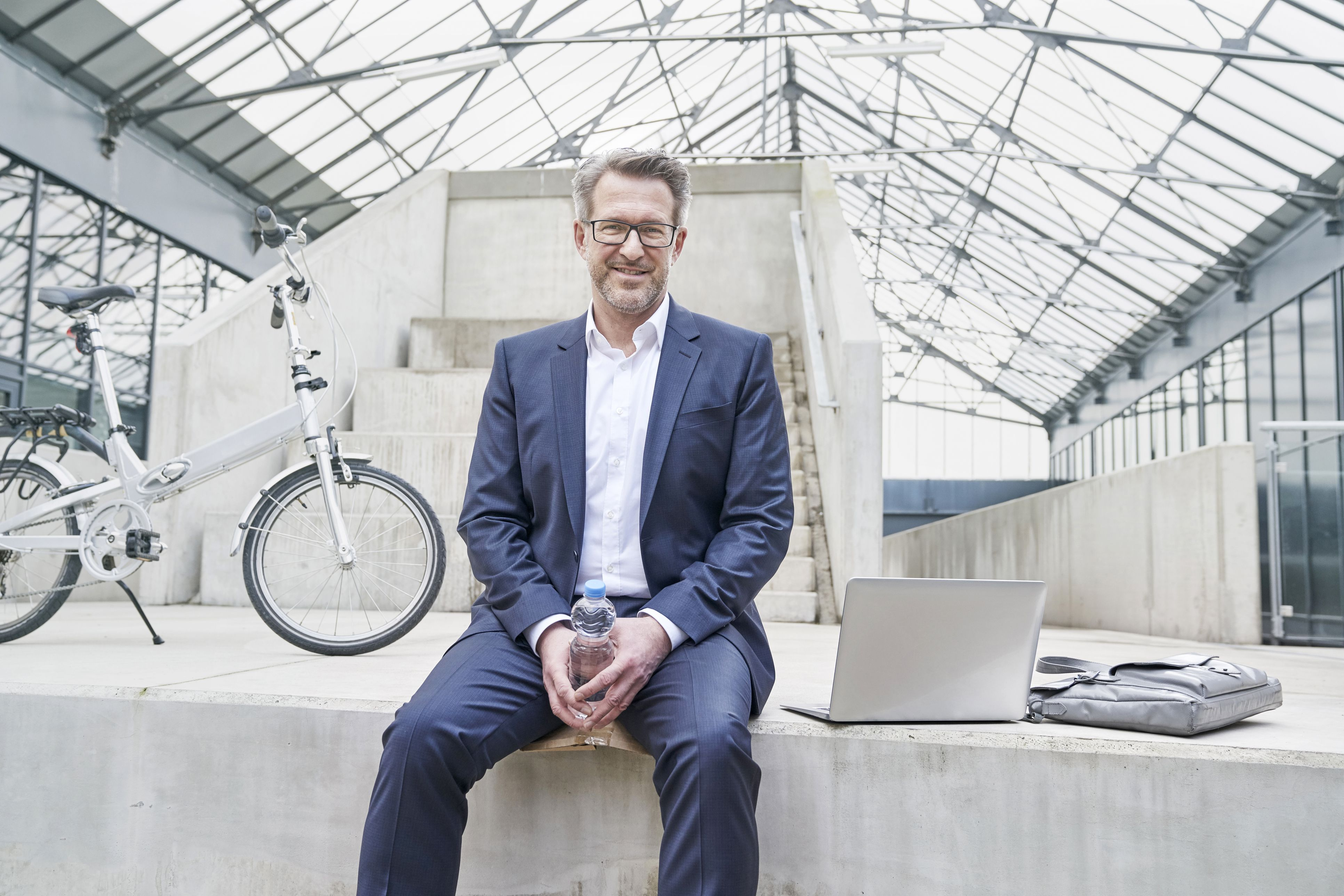 Portrait of smiling businessman sitting on wall