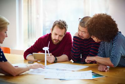 Group of professionals working together to solve a design problem on a wind turbine.