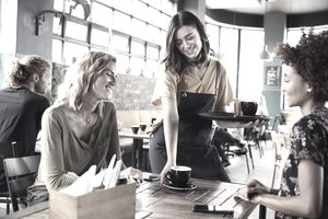 Two Female Friends Sitting At Table In Coffee Shop Being Served By Waitress