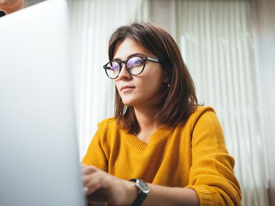 Pensive business woman wearing glasses at workplace in office. Young handsome female worker using modern laptop