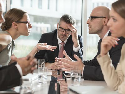 Tense meeting with coworkers visibly disagreeing with each other