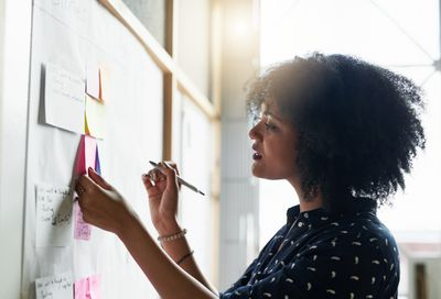 Woman setting goals and making plans with adhesives on whiteboard