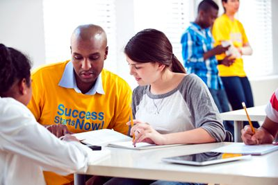 A social worker and children complete an assignment.
