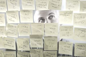 Man looking at to-do list of post-it notes stuck all around his head.