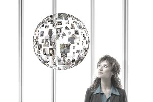 Businesswoman With Floating Globe of Faces