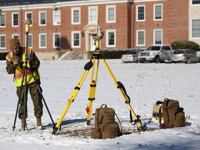 Geographic Intelligence Specialist setting up equipment outside a building on a snow covered field.