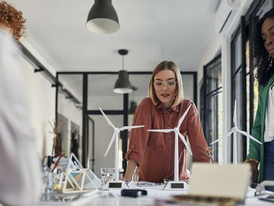Businesswomen having a meeting in office with wind turbine models on table