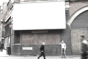 A blank billboard on a city street corner as pedestrians pass by