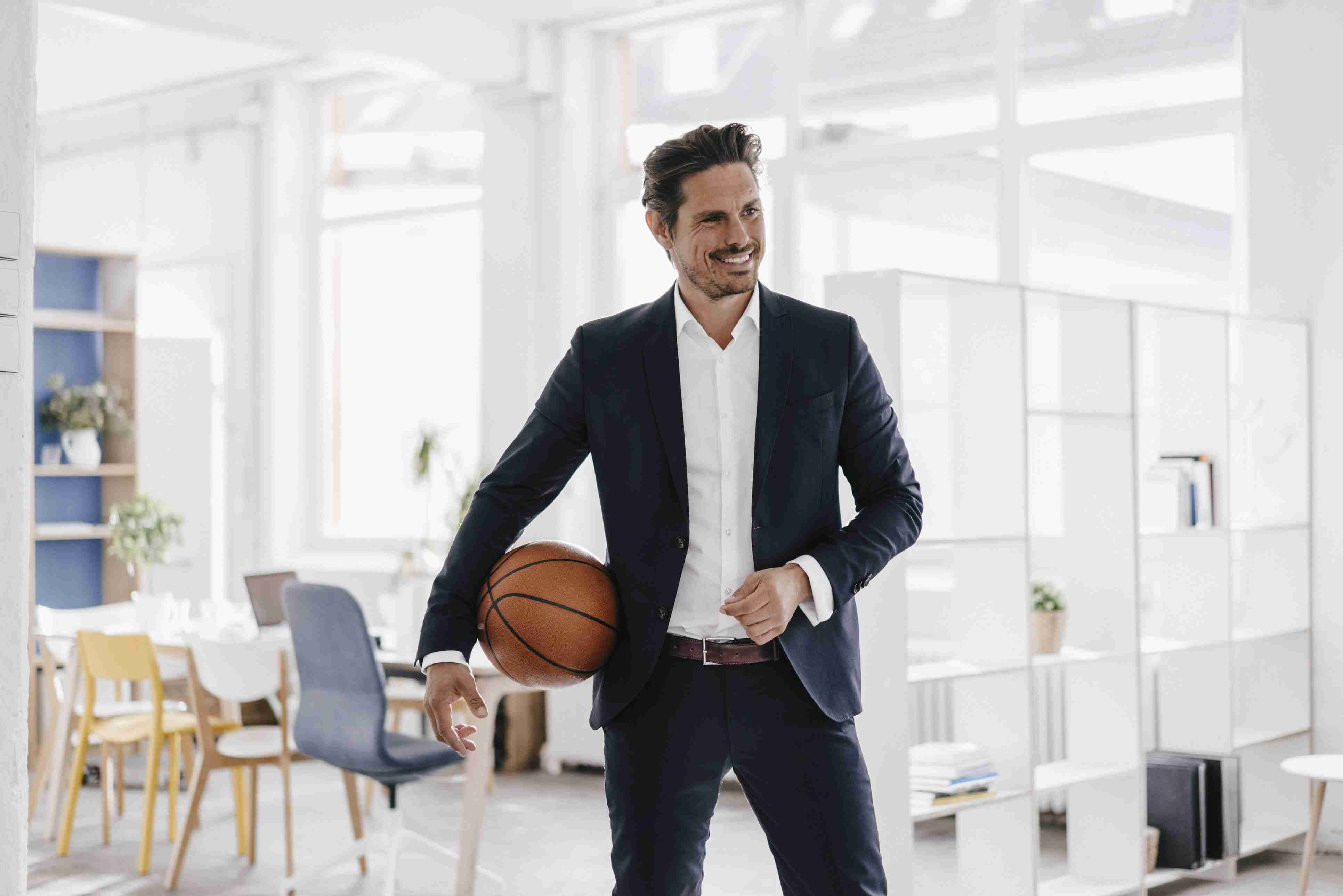 Businessman holding basketball in office