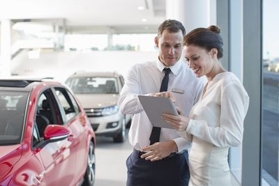 Salespeople in car dealership reviewing the weekly sales advertisement on a tablet device.