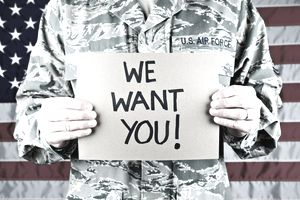 """man in Air Force uniform holding """"we want you!"""" sign"""