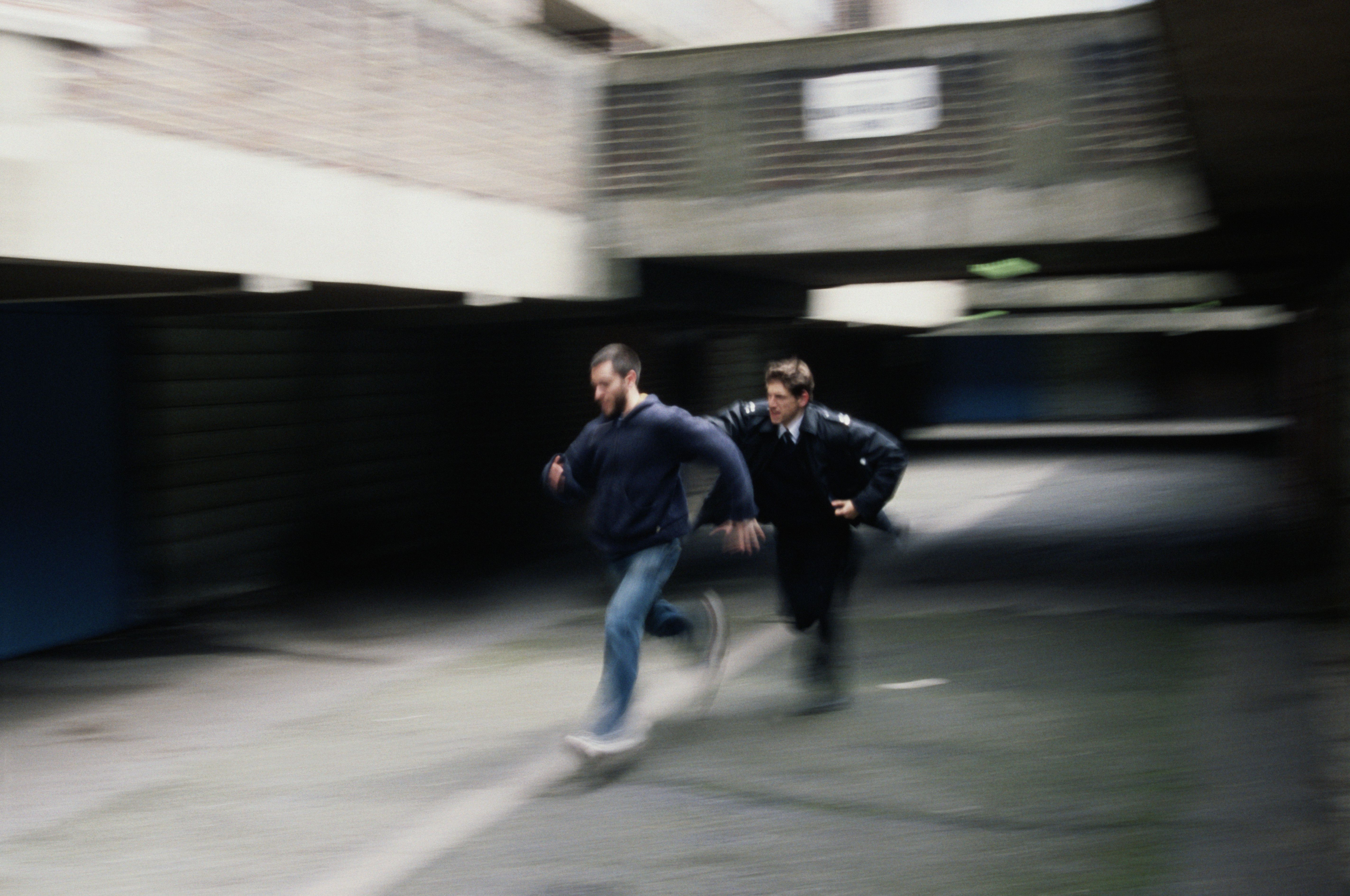 Policeman chasing and reaching for man (blurred motion)