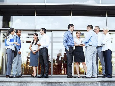 Group of businesspeople standing in front office building