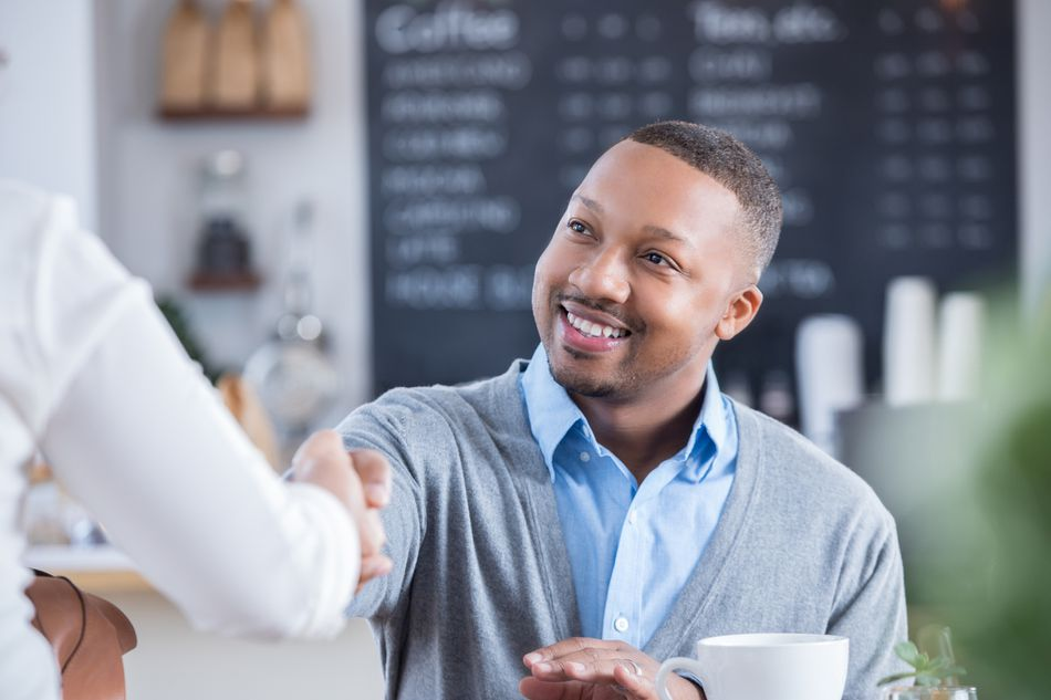Businessman meets interviewee in coffee shop