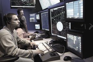 Air traffic controllers working at screens in an Air Traffic Command Center.