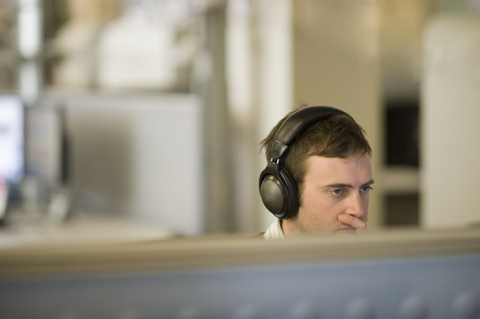 Man with headphones in cubicle
